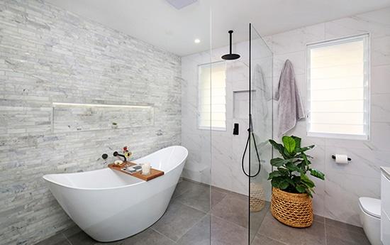 Badkar och dusch bakom helglasvägg.